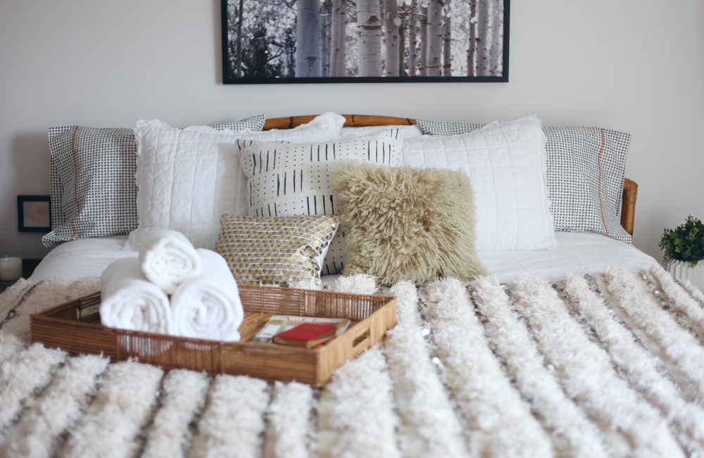 Decorist Design Project. Before and After guest bedroom reveal. Wicker tray from West Elm filled with white fluffy towels. sits on a handira wedding blanket, welcoming guest for their overnight stay. Sheepskin pillow from Chairish.