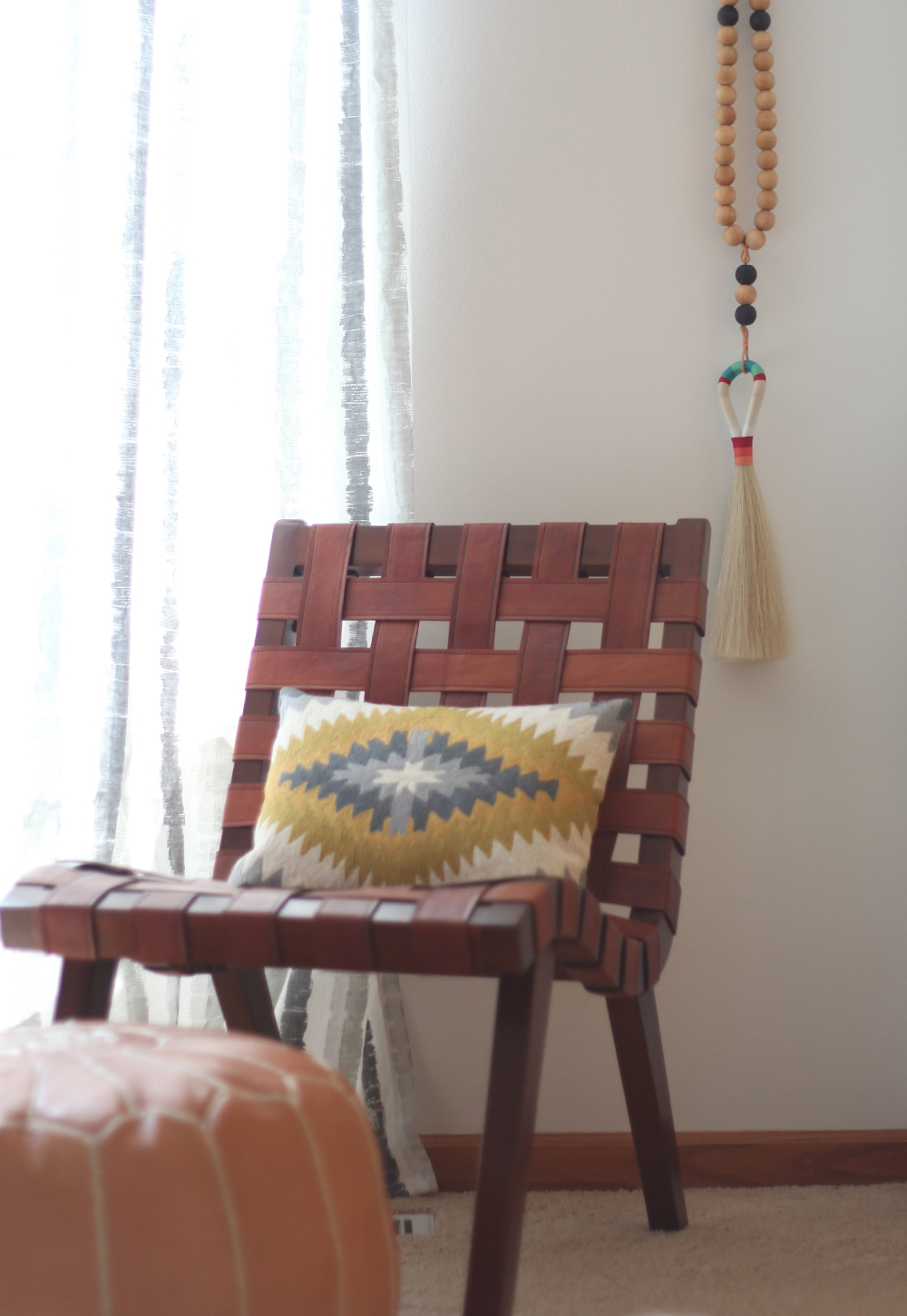Decorist Design Project. Before and After guest bedroom reveal. A worry bead necklace from Frederick and Mae is hung from a vintage fox hook. And a leather woven chair from Urban Outfitters draws in more texture to the neutral and white room.