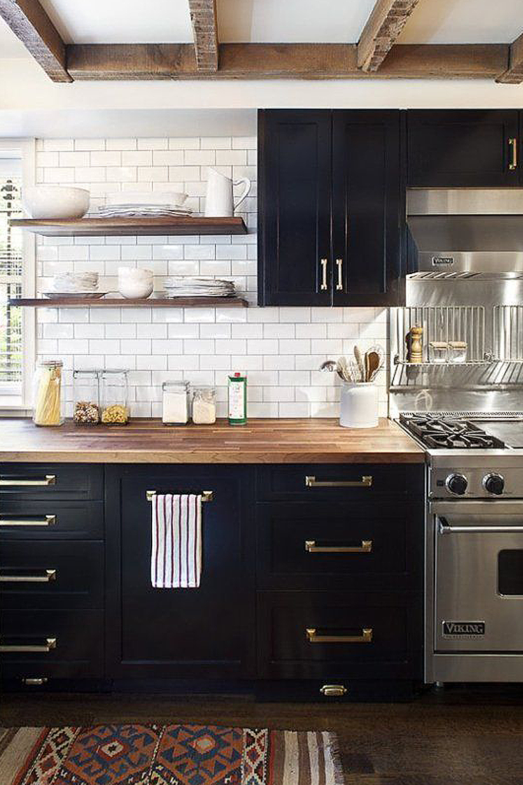 Favorite Kitchens of 2015 - This in my opinion was the best kitchen of 2015. The black and white two toned cabinetry is a perfect mix of drama and fresh and clean. It's very modern yet the industrial stainless steel stove adds a vintage feel. I also love the floating shelves.