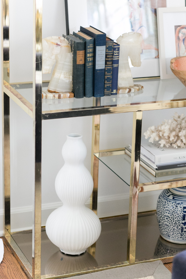 Decorist DesignOff with Jojotastic. Jonathan Adler vase and brass etagere styling. from South Loop Loft. Shelfie. Shelf styling with vintage marble horse head bookends from The Savoy Flea.
