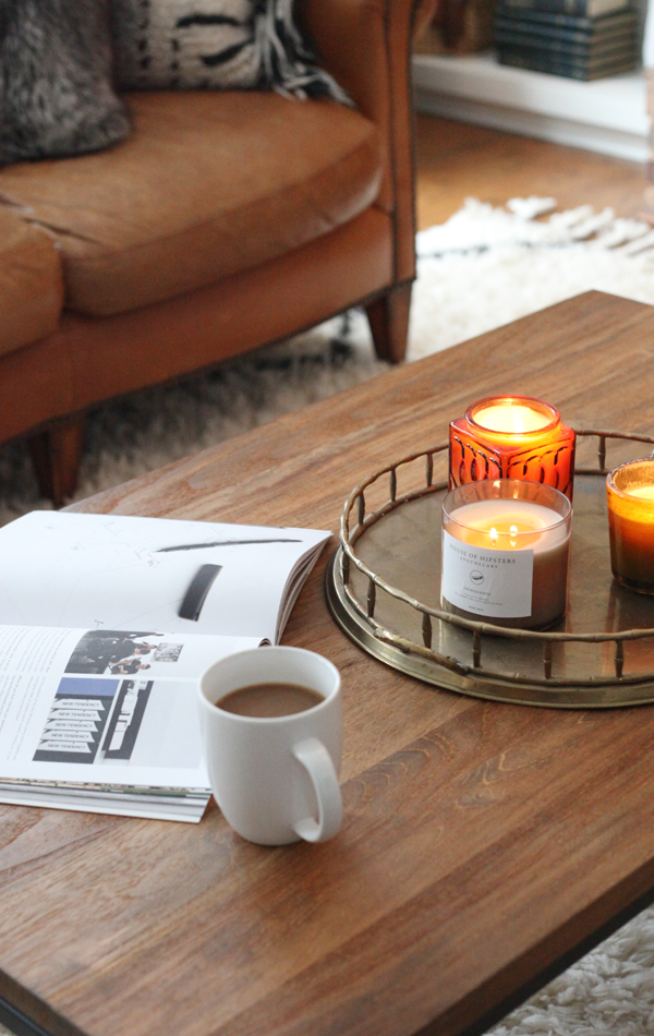 Cozy coffee table styling. candle grouping on a vintage brass tray.