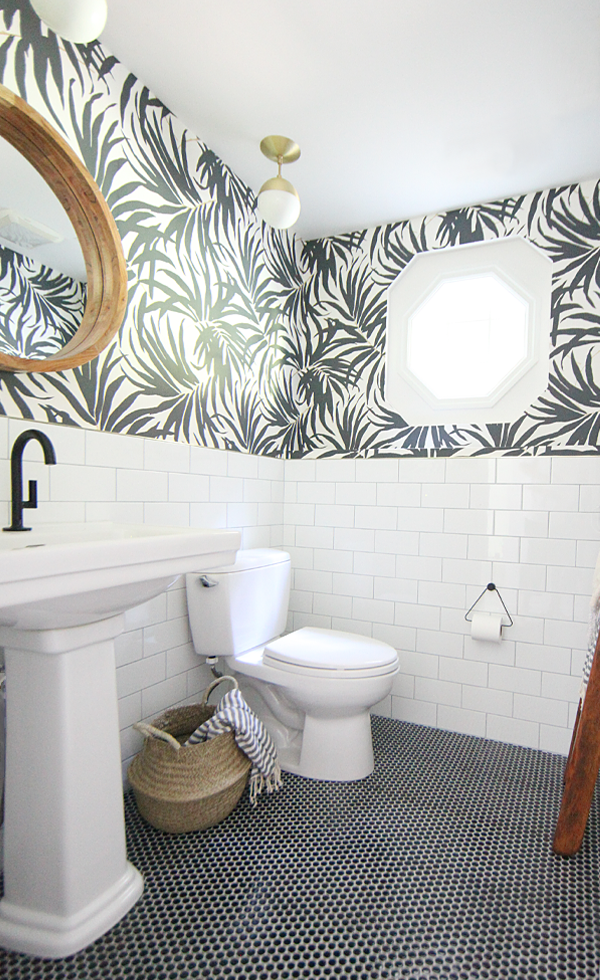 Black and white wallpaper in bathroom with brass accents, white subway tile, and black penny tile.