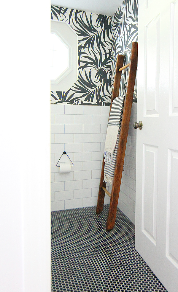 Basement Bathroom Makeover - White subway tile and black penny tile on the floor pairs with bold black and white palm leaf wallpaper. I love the hits of brass. House Of Hipsters