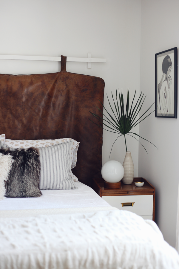Vintage gym mat leather headboard in bedroom. Neutral decor.