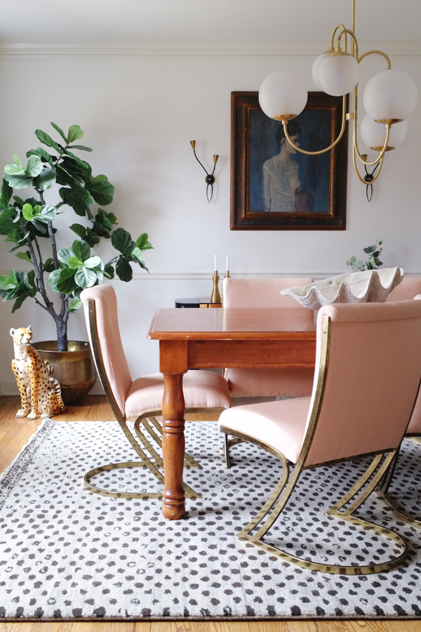 No Makeup Home Tour — Dining room makeover idea - vintage pink and brass cantilever chairs, wood farmhouse style table, modern neutral rug