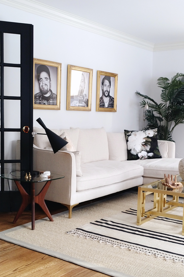 No Makeup Home Tour - House of Hipsters Living Room - mug shot artwork by Lani Lane white sofa, black trim french doors, black and white rug, brass coffee table- modern boho chic