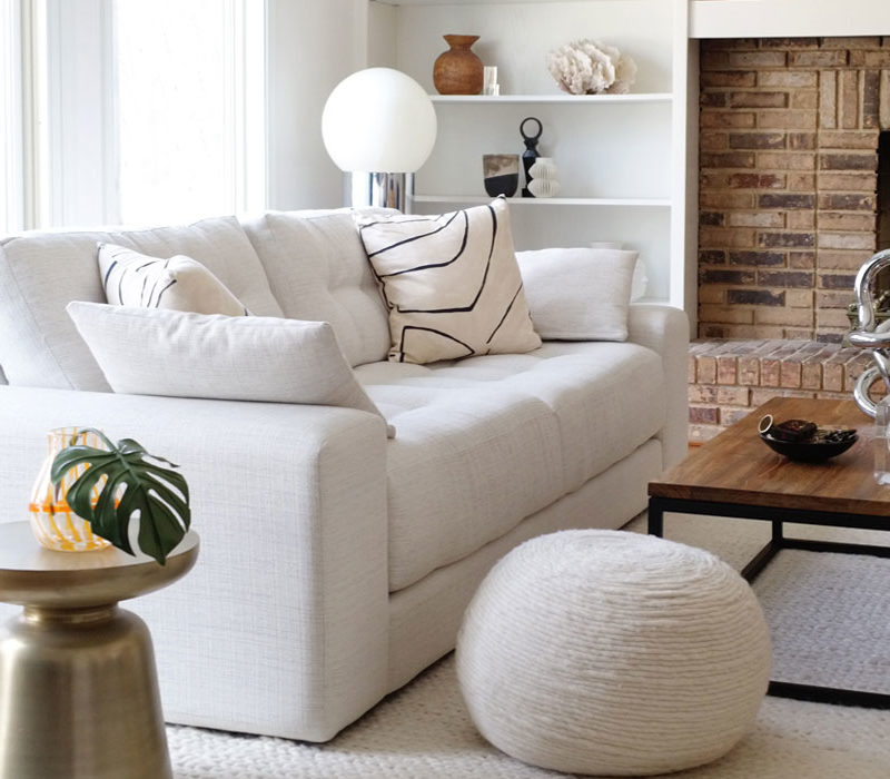 Farmhouse inspired living room with white sofa and white walls.