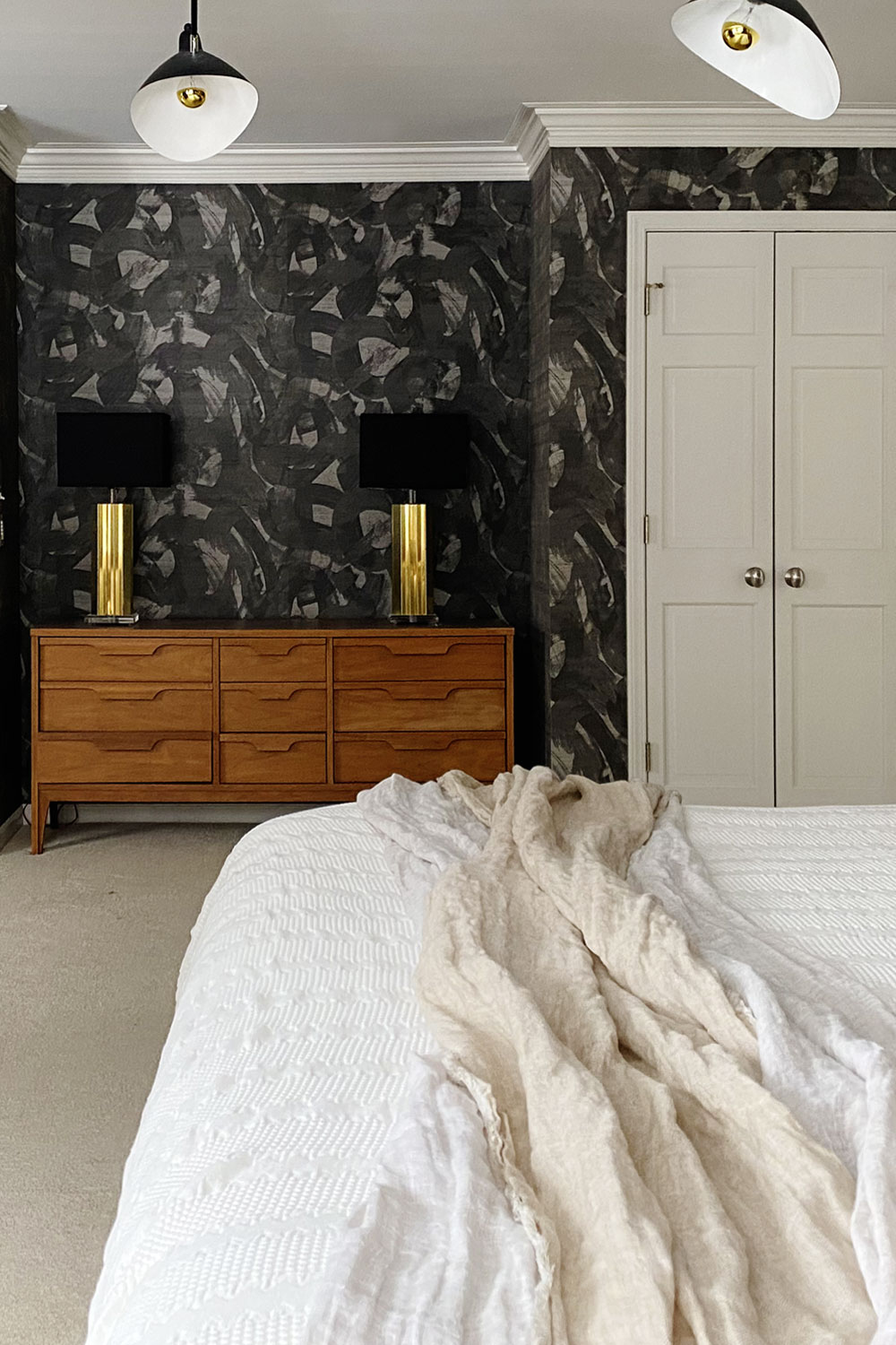 Black textured wallpaper in the bedroom with Phillips Jeffries Broad Strokes Scraffido Shadow. Luxury wallpaper in the primary bedroom to create a bold moody statement.